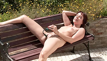 Exhibitionist brunette masturbates on a bench