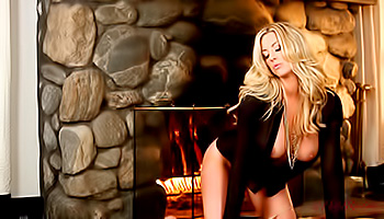 Gorgeous blonde poses beside her fireplace