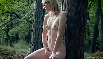 Slim blonde masturbates in the woods