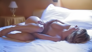 Naked blonde lies on her bed